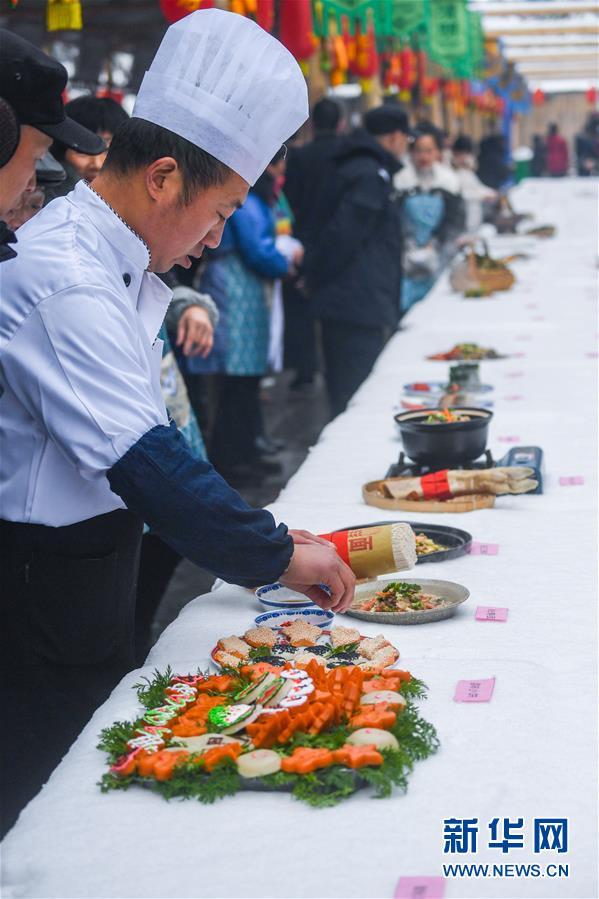 12月31日,厨师把一道刚刚烹饪完善的传统美食摆上长桌。 新华社记者徐昱摄