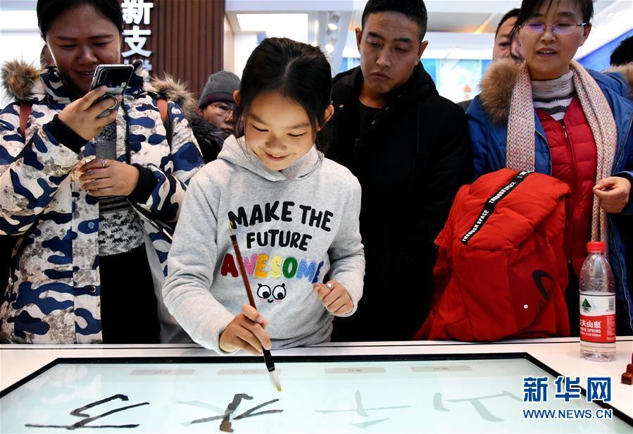 12月31日,别名女孩在体验由中科院研发的毛笔书法柔件体系。 新华社记者 潘旭
