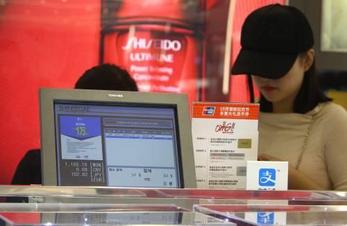 图为在韩国首尔一家免税店,新濠天地博彩娱乐官网者在柜台前付款。新华社