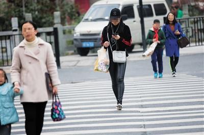 2017年11月28日,杭州市一条马路上,市民看手机过斑马线. 图/视觉中国