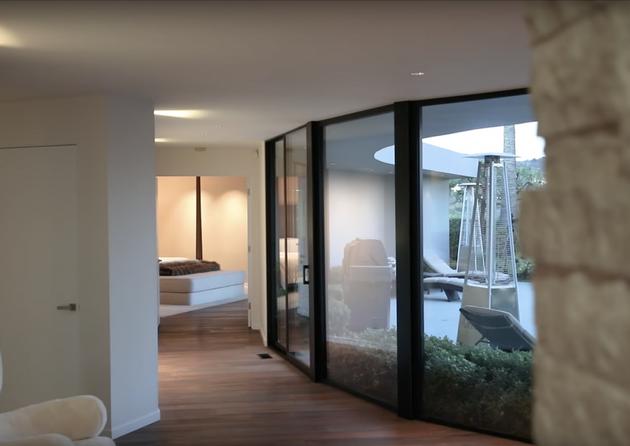 3000平方英尺的房子采用宽敞的开放式设计,比如厨房与客厅相连。滑动玻璃门通向游泳池,彩绘砖墙让人有一种身处户外之感,即便实则仍在室内。