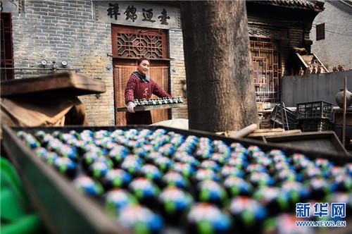 """3月5日,河南省浚县杨玘屯村,民间艺人正在搬运制作好的""""泥咕咕""""泥塑工艺品。"""