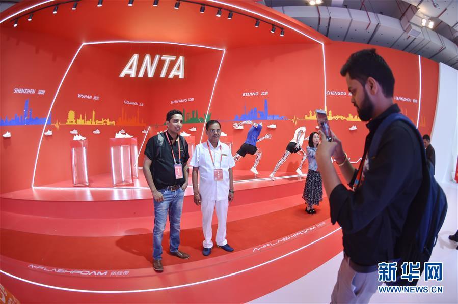 在一年一度的中国(晋江)国际鞋业暨国际体育产业博览会上,来自印度的客商在安踏展位前留影(2018年4月19日摄)。新华社记者 宋为伟
