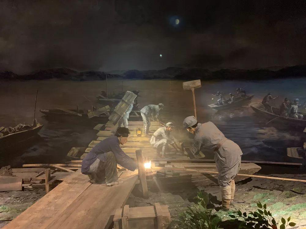 中间红军长征起程祝贺馆中表现了军民为避免敌机侦察被发现,在夜晚搭建浮桥的场景