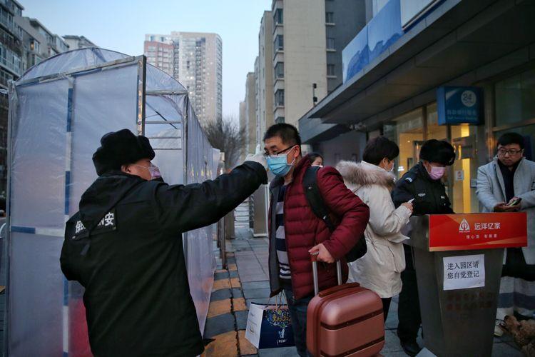 小区保安为一位进小区的居民测量体温。