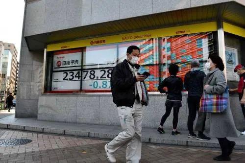 2月21日,在日本东京,路人走过街边的电子股指信休表现屏。(新华社/法新)
